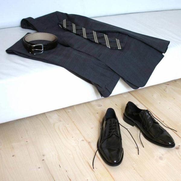 Klassischer Herrenschuh aus schwarzem, poliertem Leder mit grauem Anzug auf Couch 10