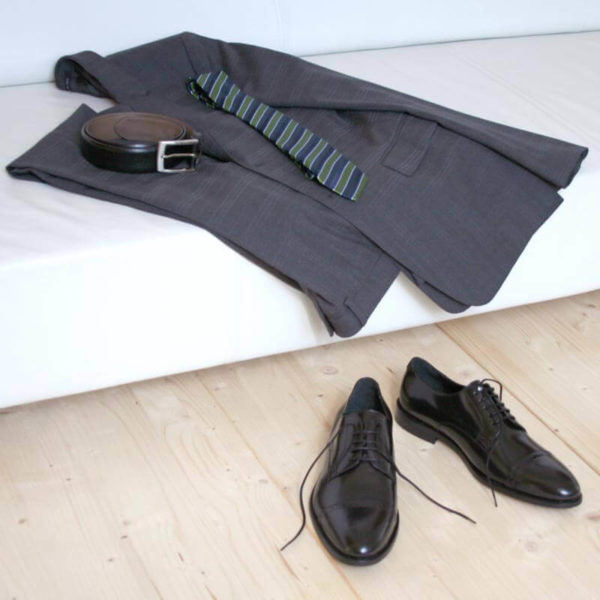 Klassischer Herrenschuh aus schwarzem, poliertem Leder mit grauem Anzug auf Couch 5