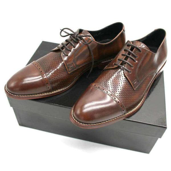 Foto von zwei braunen Herrenschuhen Modell Komfortabler Klassiker mit Teilperforation und schlichter Zehenkappe auf schwarzem Schuhkarton_323-1