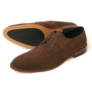 Foto von zwei dunkelbraunen Wildleder Derby Herrenschuhen nach links zeigend - ein Schuh liegt auf der Seite, so dass die Sohle zu sehen ist. Modell Leger italienisch