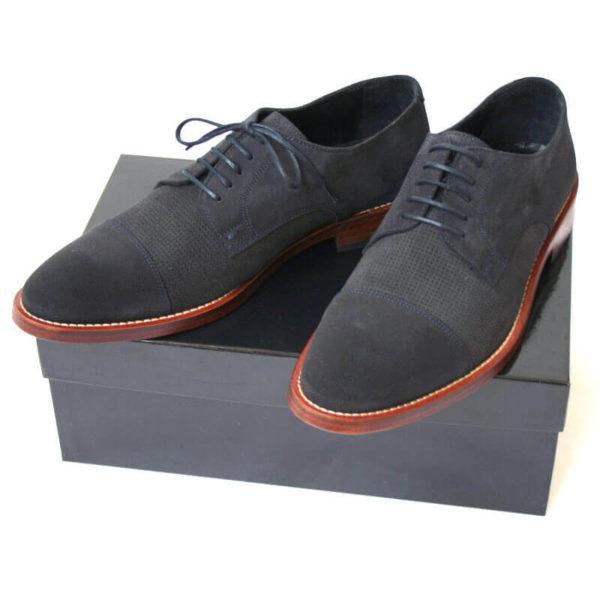 Foto von zwei dunkelblauen Wildleder Herrenschuhen auf schwarzem Schuhkarton. Modell Legere elegant