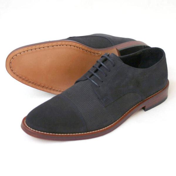 Foto von zwei dunkelblauen Wildleder Derby Herrenschuhen nach links zeigend - ein Schuh liegt auf der Seite, so dass die Sohle zu sehen ist. Modell Legere elegant
