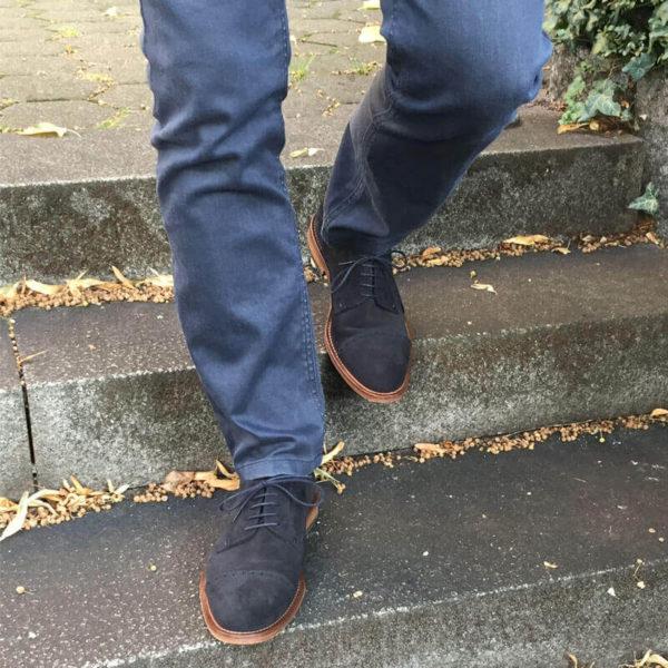 Foto Herrenbeine mit dunkelblauen Wildleder Derby Herrenschuhen, Modell Legere elegant, gehen Treppe hinunter.