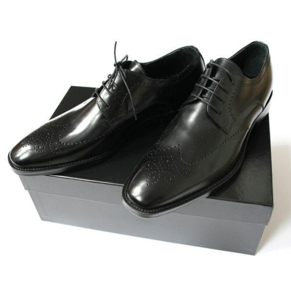 Foto zeigt das Produkt Maskuliner Klassiker Herren-Businessschuh in Schwarz mit eleganter Verzierung auf schwarzem Schuhkarton