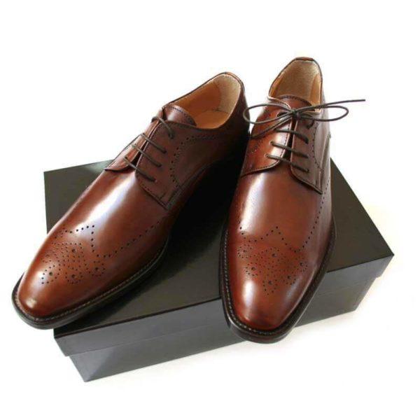Foto-2 kastanienbraune Business Herrenschuhe mit Lochverzierung auf schwarzem Schuhkarton.