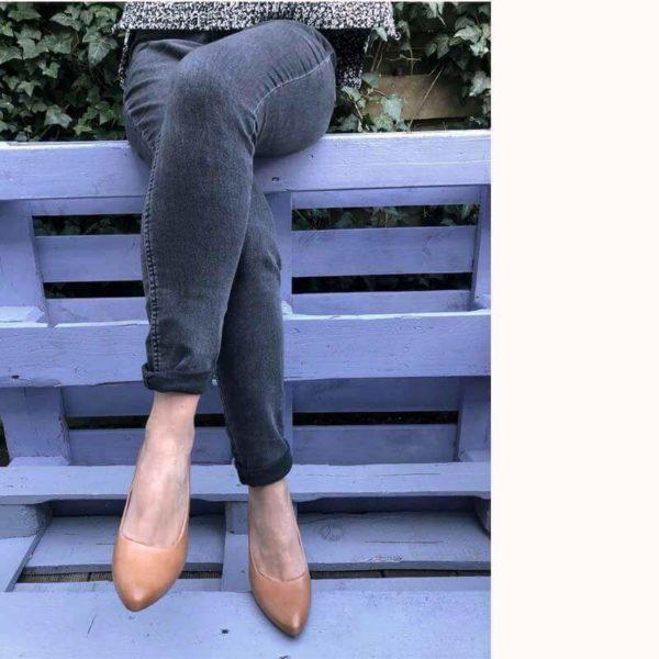 Foto Pumps Cognac an übereinandersgeschlagenen Beinen mit blauem Hintergrund_Modell 531
