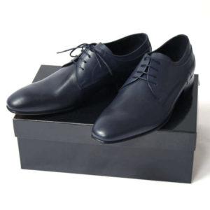 Foto von zwei dunkelblauen Glattleder Derby Herrenschuhen auf schwarzem Schuhkarton. Modell Stadt Eleganz