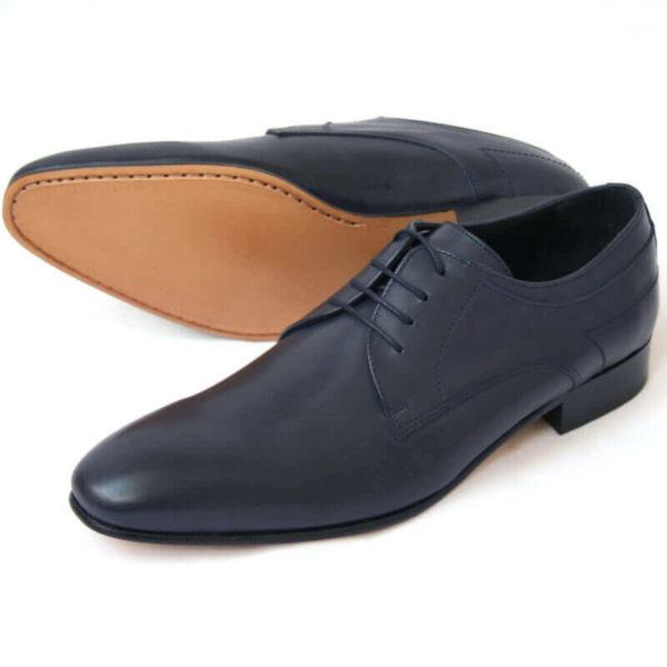 Foto von zwei dunkelblauen Glattleder Derby Herrenschuhen nach links zeigend - ein Schuh liegt auf der Seite, so dass die Sohle zu sehen ist. Modell Stadt Eleganz