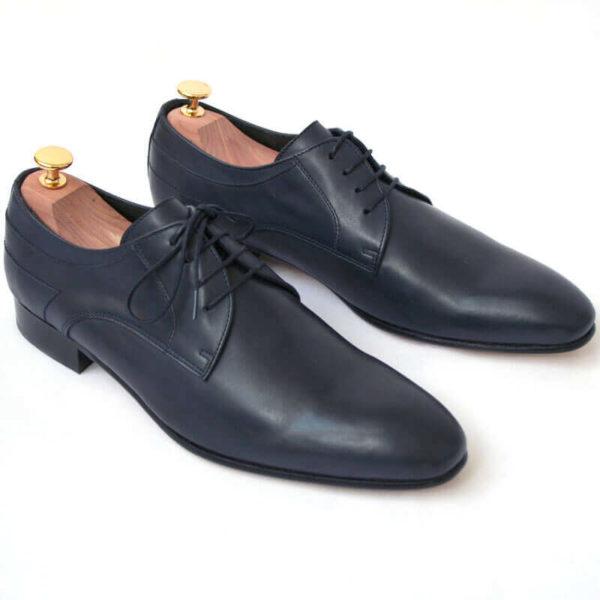 Foto von zwei dunkelblauen Glattleder Derby Herrenschuhen nach schräg unten rechts zeigend mit Goldkopf-Schuhspannern. Modell Stadt Eleganz