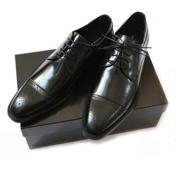 Foto-Herren Business Schuhe-Halfbrogue. 2 schwarze Schuhe auf schwarzem Schuhkarton. Modell Stattliche Eleganz