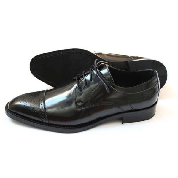 Foto-Herren Business Schuhe-Halfbrogue. 1 Schuh zeigt nach links mit der Spitze, der andere liegt, so dass die Sohle zu sehen ist.