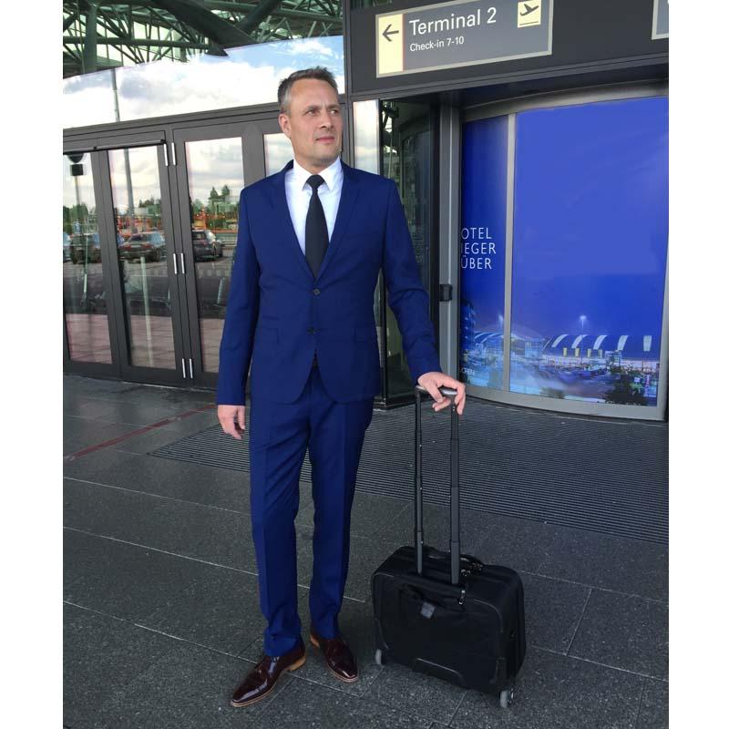 Foto: Geschäftsmann außerhalb des Flughafens stehend mit Rollkoffer. Blauer Anzug und Herrenschuhe in Bordeaux Stilsicherer Begleiter