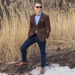 Foto von einem Mann mit Sonnenbrille am Strand im Hinterrund Schilfgras. Trägt Business Casual Outfit und an den Füßen Topmodischer Allrounder Business Herrenschuhe
